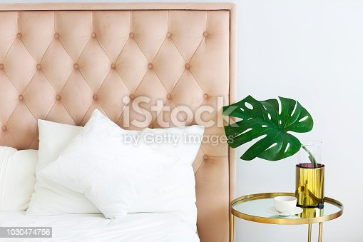 Modern bedroom with table side and pillows and coffee. Closeup