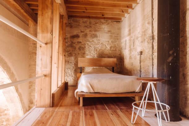 moderne schlafzimmer mit holz und stein in rustikalen hütte - cottage schlafzimmer stock-fotos und bilder