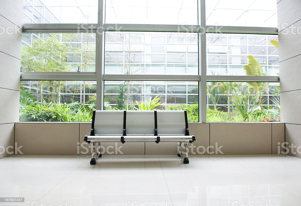 A modern bench in a brightly lit room with windows stock photo