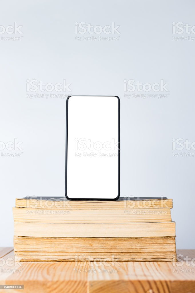 Modern bezel less smart phone on pile of books. stock photo