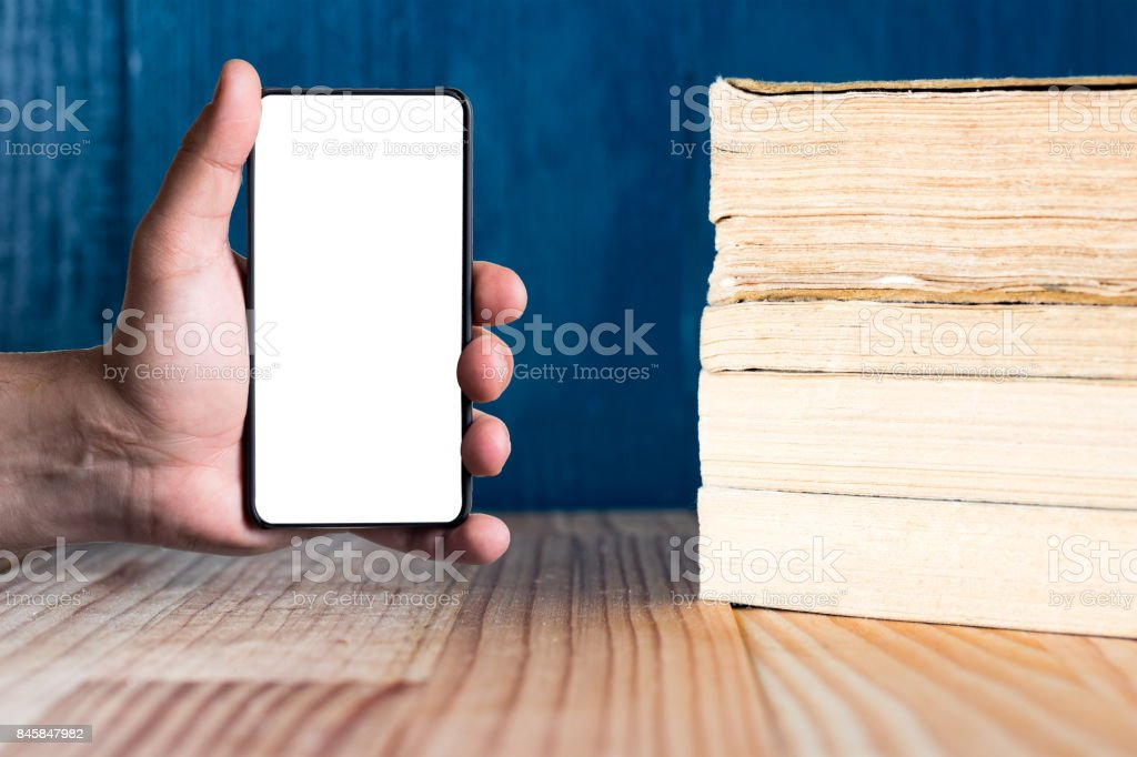 Modern bezel less smart phone with pile of books. stock photo