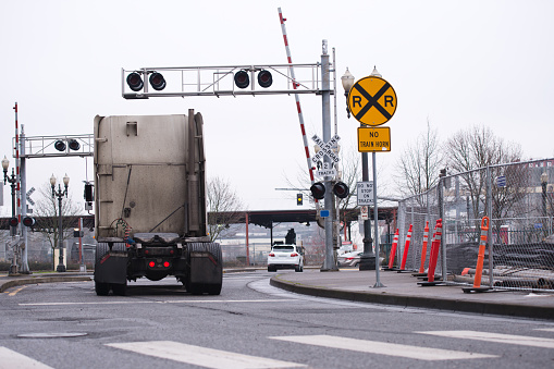 A dirty semi truck tractor without a trailer crosses an open railroad crossing with warning signs and traffic lights along the road with construction restrictive cones along one side and a pedestrian crossing lines.