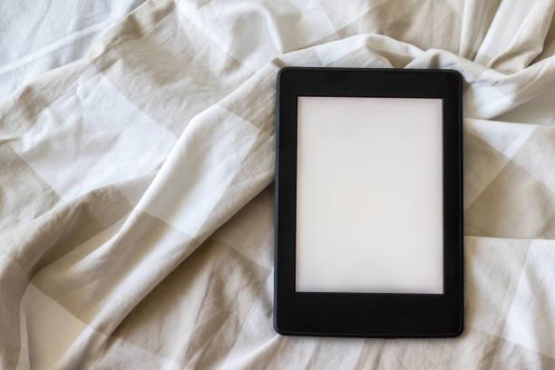 Un livre électronique noir moderne avec un écran vide vide sur un lit blanc et beige. Comprimé de maquette sur la literie - Photo