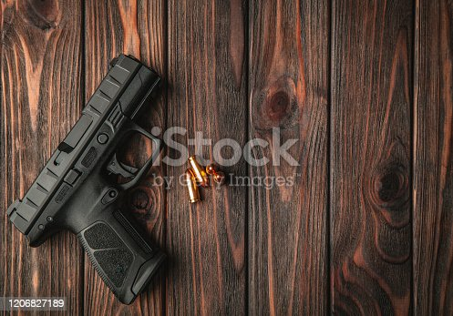 Modern black gun and ammunition  on a wooden background. Pistol. Weapons for sport and self-defense lie on the table.