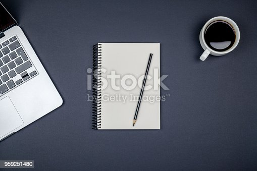istock Modern black office desk table with laptop and blank notebook page for input the text. Top view, flat lay 959251480