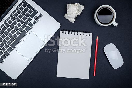 istock Modern black office desk table with laptop and blank notebook page for input the text. Top view, flat lay 959251642
