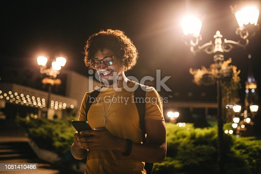 Handsome casually dressed student, returning from a night school and texting.
