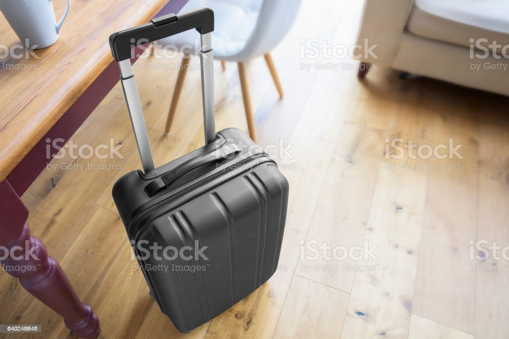 Modern black suitcase beside a table and chairs stock photo
