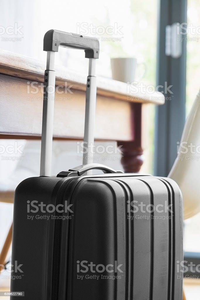 Modern, black wheeled suitcase beside a table and chairs stock photo