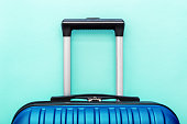 Modern Blue classic blue suitcase on blue background close up with copy space for text. Minimal style travel concept. Vacation trip. Summer holiday stock photo. Trendy color 2020 classic blue.