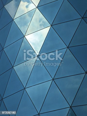 close up of a modern corporate building with angular patterned mirrored windows panes reflecting the sky and clouds