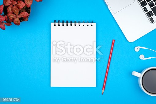 istock Modern blue office desk table with laptop and blank notebook page for input the text. Top view, flat lay 959251734