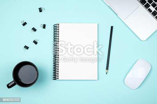 istock Modern blue office desk table with laptop and blank notebook page for input the text. Top view, flat lay 959252222
