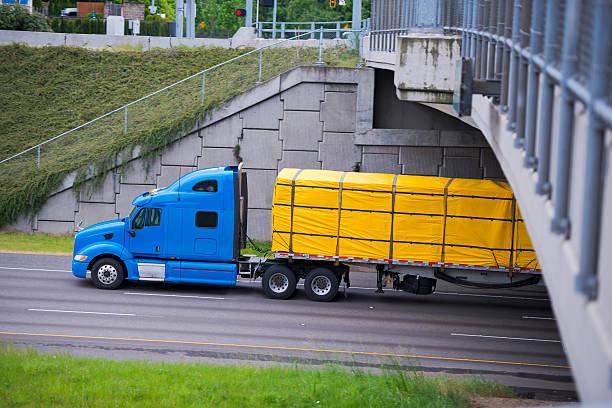 modernes blau semi truck mit gelben umschlag cargo auf dem anhänger - planenzelt stock-fotos und bilder