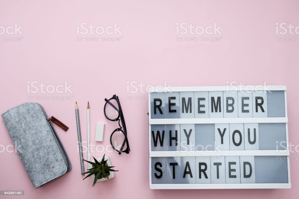 Modern Board with text Remember why you started, plant, phone, sheet, pencils, candy on a pink background. Top view, flat lay, space for text stock photo