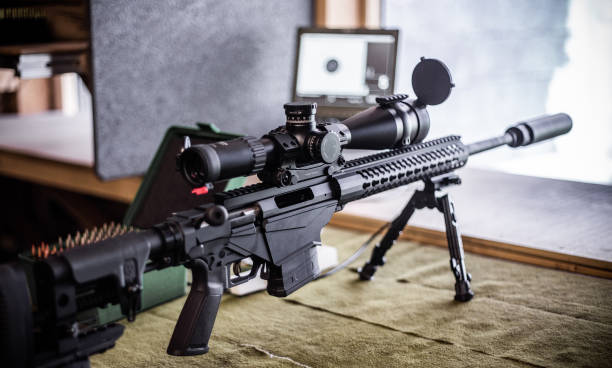 Modern bolt action rifle with scope and suppressor stock photo