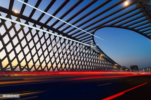 Modern bridge in the sunset with Car track
