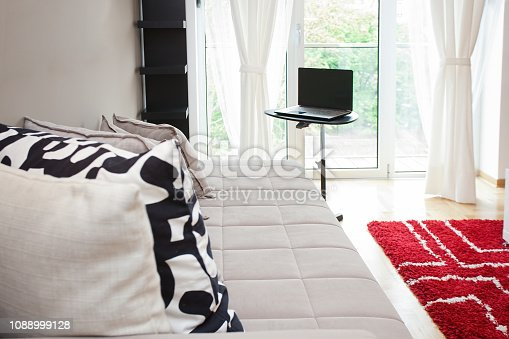 istock Modern bright apartment view with sofa and laptop 1088999128