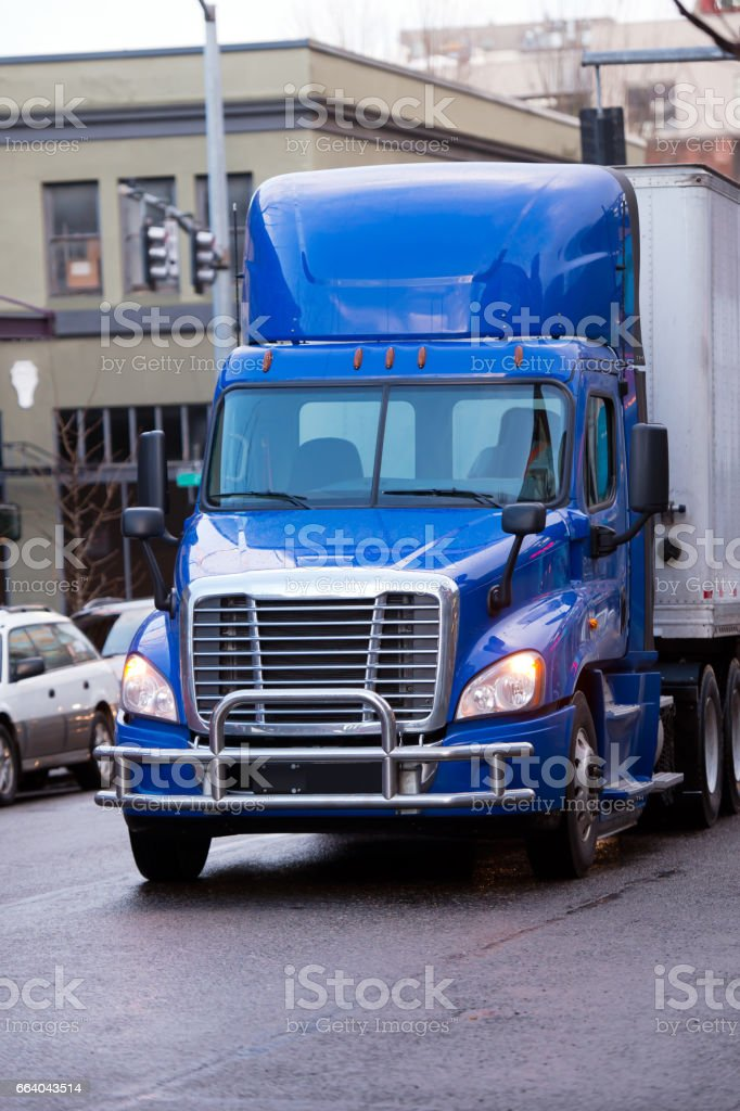 Modern bright blue semi truck with trailer and bumper Protection on city street stock photo