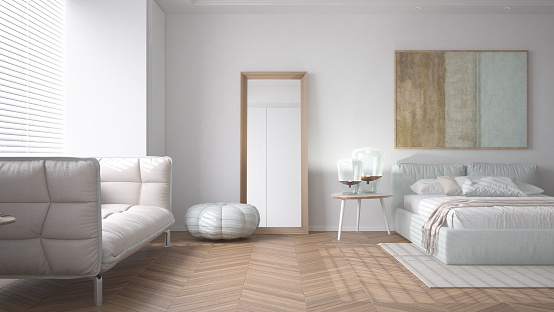 Modern bright minimalist bedroom in white tones, double bed with pillows, duvet and blanket, parquet, window and sofa, table with lamps, mirror with pouf, carpet, interior design idea