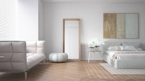 Modern bright minimalist bedroom in white tones, double bed with pillows, duvet and blanket, parquet, window and sofa, table with lamps, mirror with pouf, carpet, interior design idea stock photo