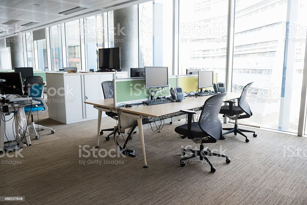 A photo of empty workplace. Computers and chairs are arranged at...
