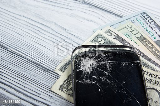 istock Modern broken mobile phone and money on white wooden background. 484164150