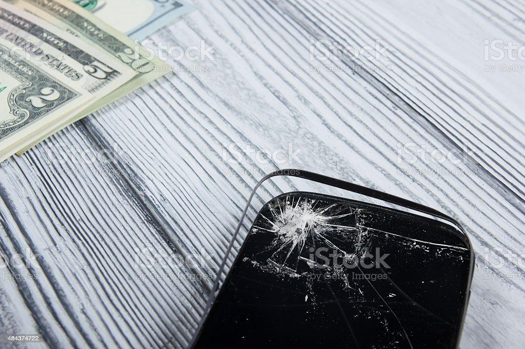 Rotto Moderno Telefono Cellulare E Soldi Su Bianco Sfondo In Legno