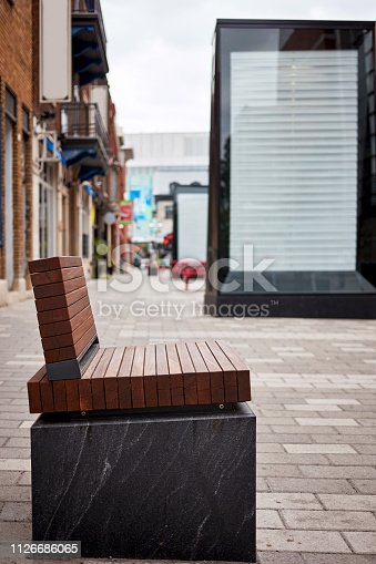 istock Modern brown wooden bench and empty billboard on the sidewalk 1126686065