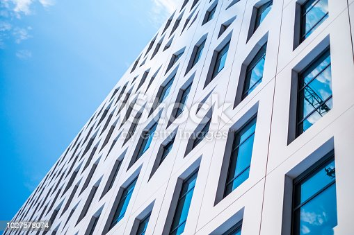 istock modern building with many glass windows in which the sky reflects 1027578074