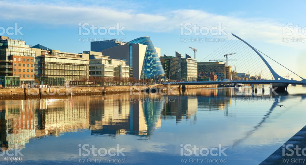 Modern buildings on Liffey river in Dublin and Harp bridge stock photo