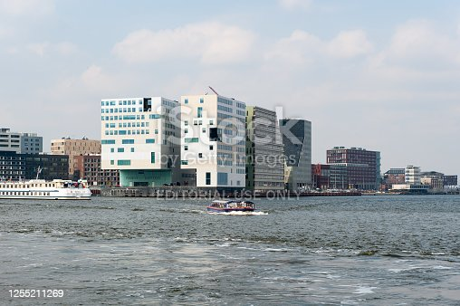 A view at the modern office buildings and apartments on the south bank of the river IJ in Amsterdam. This area on the West side of the Central Railway Station is locally called \