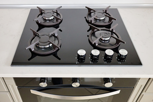 Modern built-in oven and gas stove classic design in dark tones under light stone marble or granite countertop, in interior of contemporary kitchen.