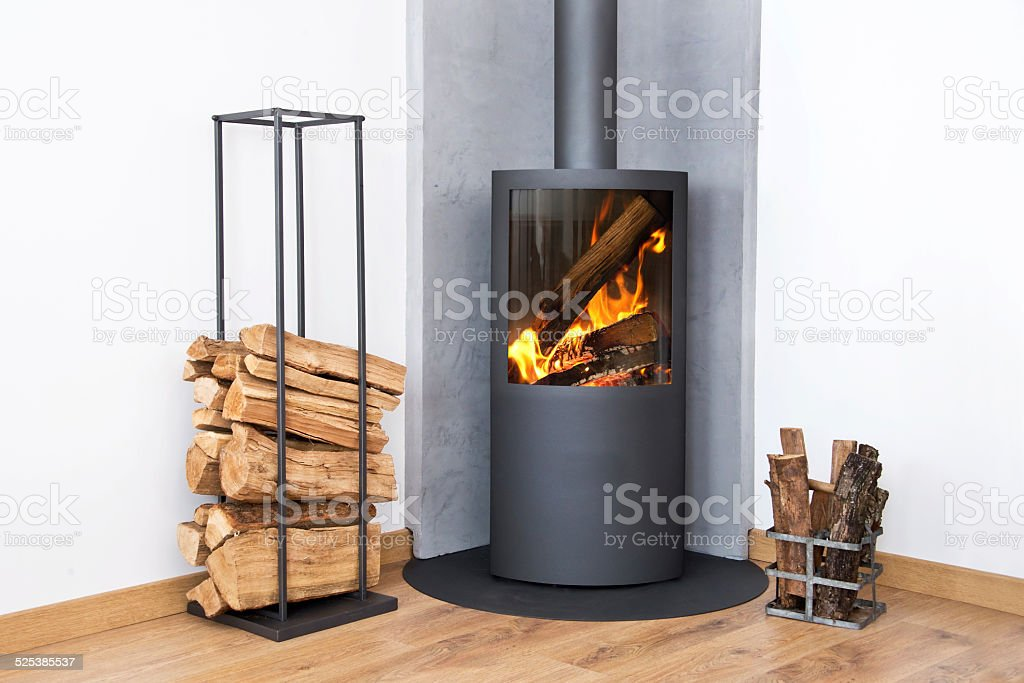Modern burning stove next to a wood logs rack stock photo