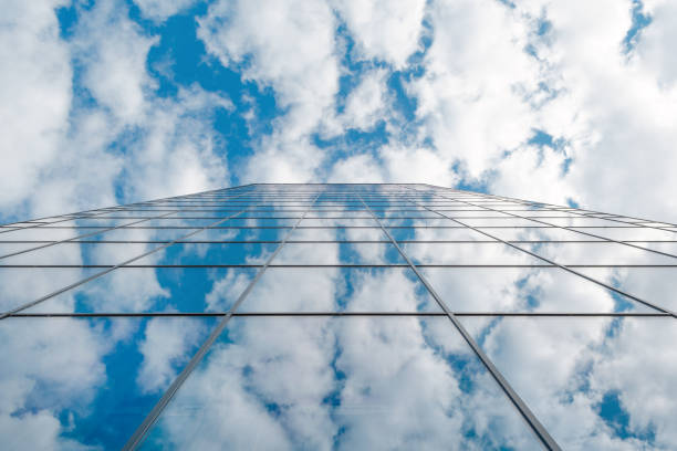 modern business high rise glass building and blue sky with clouds stock photo