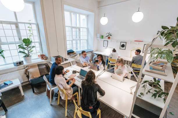 Modern business office with multi-ethnic team Coworkers working in modern co-working space in Scandinavia. Multi-ethnic group of young business professionals, start-up establishers, freelancers working and developing together. customs stock pictures, royalty-free photos & images