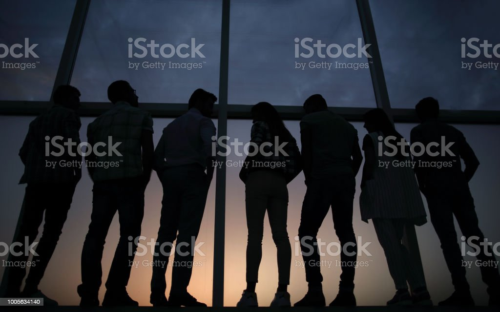 modern business team standing near a large window stock photo