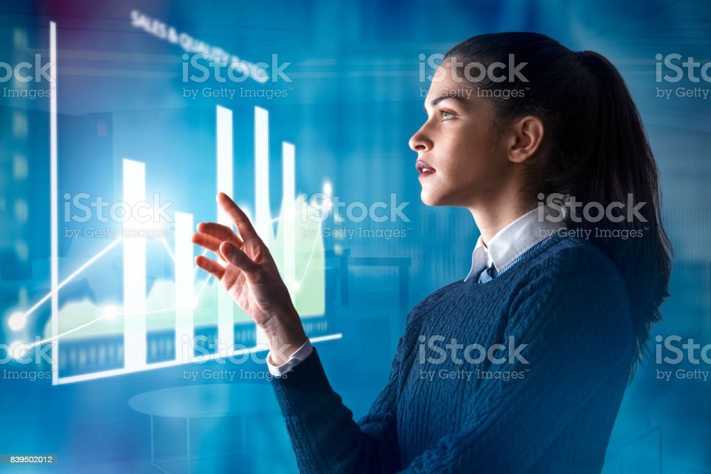 modern business woman using innovative technologies to manage her administrative work, analyzing a digital projected graph stock photo