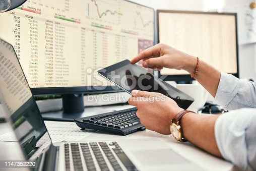 istock Modern businessman. Cropped photo of young trader in formal wear and watch on his hand using digital tablet and analyzing data while working in his office. 1147352220