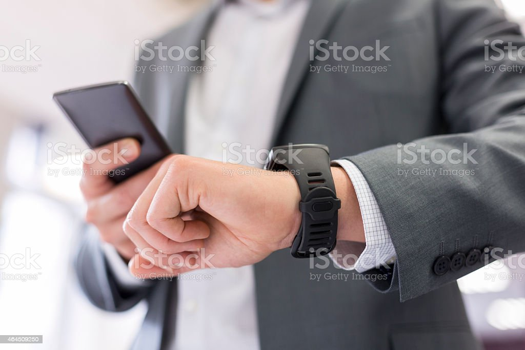 Modern businessman focused on his phone and smart watch stock photo
