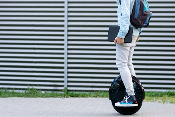 Modern businessman student freelancer riding on ecological electric transport Modern young adult male businessman student freelancer with backpack and laptop riding on ecological electric transport futuristic eco electric unicycle scooter, balancing electric wheel. Eco planet. on the move stock pictures, royalty-free photos & images