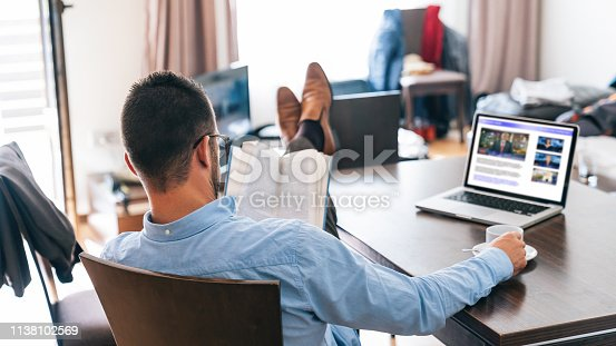 istock Modern businessman using laptop at hotel room and reading book 1138102569
