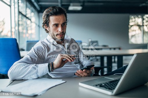 One man, modern businessman sitting in office, using smart phone.