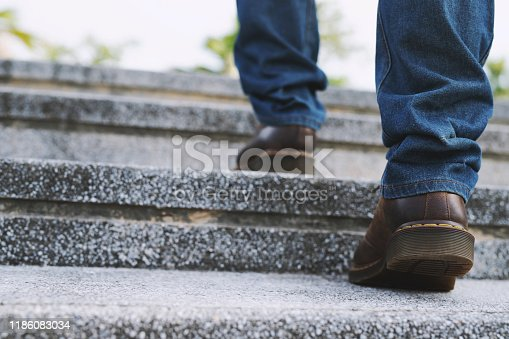 684803840istockphoto modern businessman working close-up legs walking up the stairs in modern city. in rush hour to work in office a hurry. During the first morning of work. stairway. soft focus. 1186083034