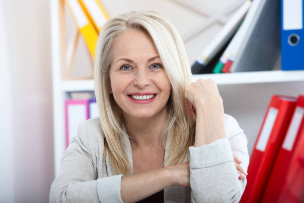 Modern businesswoman. Beautiful middle aged woman looking at camera Modern businesswoman. Beautiful middle aged woman looking at camera with smile while siting in the office. Female face close-up civil servant stock pictures, royalty-free photos & images