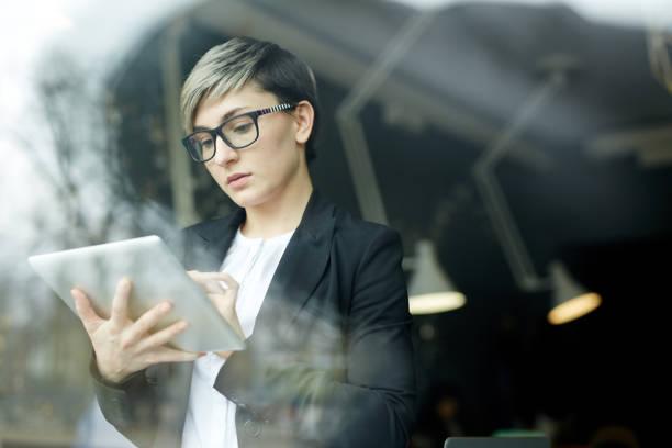 femme d'affaires moderne travaillant avec l'appareil de tablette - génération z photos et images de collection