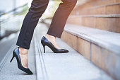 modern businesswoman working woman close up legs walking up the stairs in modern city in rush hour to work in office a hurry. During the first morning of work. Leave space for writing descriptive text