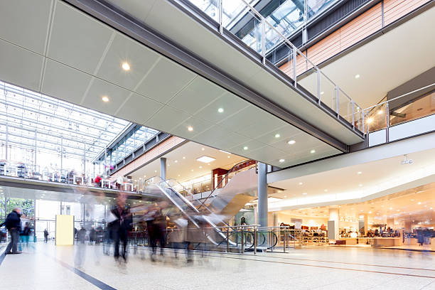 modern busy shopping mall with motion blurred shoppers - shopping mall stock photos and pictures