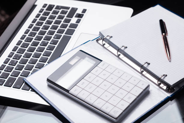Modern calculator is on a laptop and on an open notebook stock photo