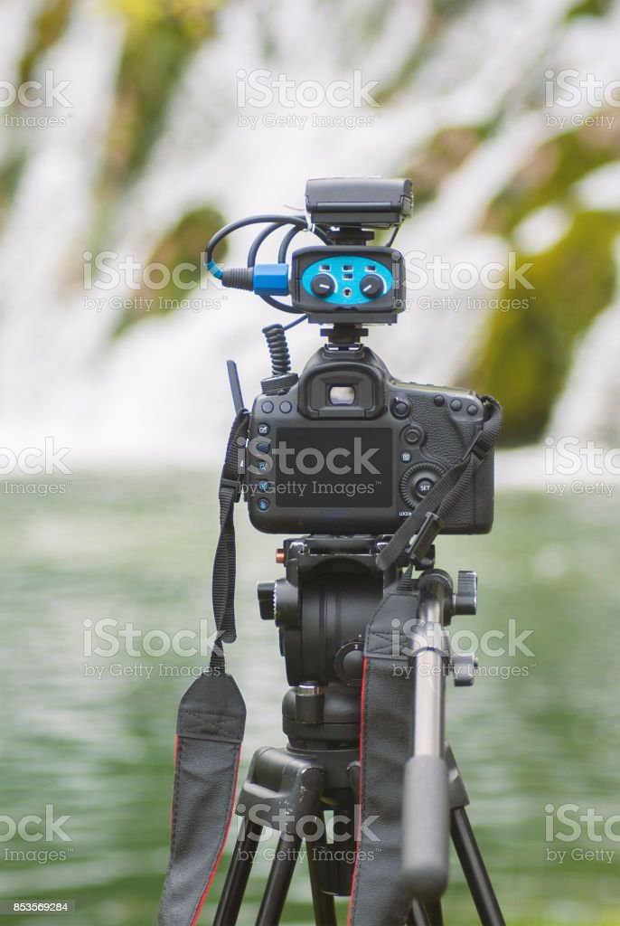 Modern camera with mic on tripod recording nature stock photo